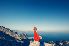 Young beautiful woman in red dress looking to mountains sea Stock Photography