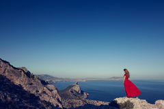 Young beautiful woman in red dress looking to mountains sea Stock Photo