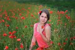 Young beautiful woman in red dress sitting in a poppy field royalty free stock image