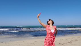 Young beautiful woman in red dress taking selfie with her camera phone on the sea beach with strong wind and waves. Slow motion.  stock video