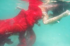 Young beautiful woman in red dress underwater. Underwater portrait of young beautiful woman in red dress Royalty Free Stock Photos