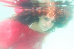 Young beautiful woman in red dress underwater. Underwater portrait of young beautiful woman in red dress Royalty Free Stock Photo