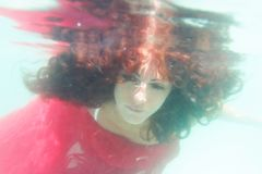 Young beautiful woman in red dress underwater. Underwater portrait of young beutiful woman in red dress Stock Image