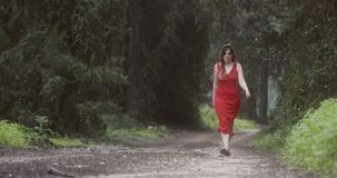 Young beautiful woman with a red dress walking in a green forest stock footage