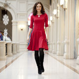 Young beautiful woman in red dress walks in the store Royalty Free Stock Photos