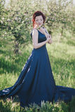 Young beautiful woman with red hair in a blue dress posing in a blooming garden Royalty Free Stock Photos
