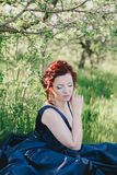 Young beautiful woman with red hair in a blue dress posing in a blooming garden Royalty Free Stock Image