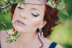 Young beautiful woman with red hair in a blue dress posing in a blooming garden Stock Photo