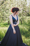 Young beautiful woman with red hair in a blue dress posing in a blooming garden Stock Photography