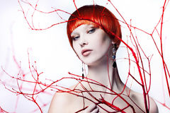 Young beautiful woman with red hair. Portrait in Studio on white background, branches of tree Stock Image