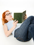 Young beautiful woman with red hair reading book Stock Photography