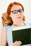 Young beautiful woman with red hair reading book Stock Image