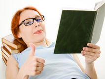 Young beautiful woman with red hair reading book Stock Photos