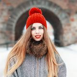 Young beautiful woman in a red hat and coat with fur on a winter Stock Photos