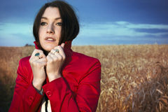 Young beautiful woman in a red jacket on a wheat field Stock Image