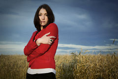 Young beautiful woman in a red jacket on a yellow wheat field Royalty Free Stock Images