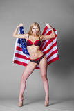 Young beautiful woman in red lingerie holding American flag Royalty Free Stock Photos