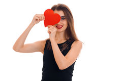Young beautiful woman with red lips preparing to celebrate valentines day with heart symbol in studio isolated on white Stock Photo