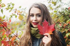 Young beautiful woman with red maple autumn leaf. Outdoors royalty free stock images