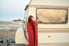 Young beautiful woman in a red plaid standing on the beach near a trailer stock photo