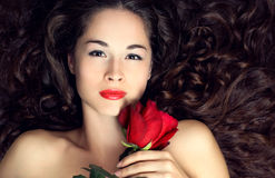 Young beautiful woman with red rose. Portrait of young beautiful woman with red rose and healthy long hair Stock Images