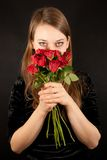 A young beautiful woman with red roses Royalty Free Stock Image