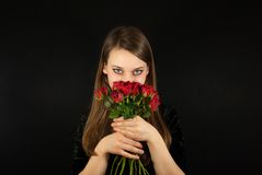 A young beautiful woman with red roses Stock Photos