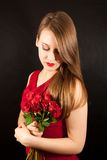 A young beautiful woman with red roses Stock Image