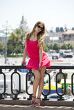 Young beautiful woman in red short dress posing outdoors in sunn Royalty Free Stock Photo
