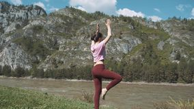 Young beautiful woman in red tank top practicing outdoors, doing Bending Tree posture, variation of Vrksasana, in park stock video
