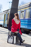 Young beautiful woman in red waiting for train on the platform Royalty Free Stock Photography