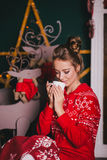 Young beautiful woman in a red warm pajamas with scandinavian ornaments sitting near decorative fireplace and drinking hot cocoa Stock Photography