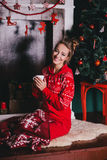 Young beautiful woman in a red warm pajamas with scandinavian ornaments sitting near decorative fireplace and drinking hot tea Stock Image