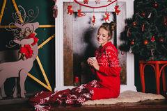 Young beautiful woman in a red warm pajamas with scandinavian ornaments sitting near decorative fireplace and drinking hot tea Royalty Free Stock Image