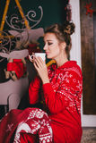 Young beautiful woman in a red warm pajamas with scandinavian ornaments sitting near decorative fireplace and drinking hot tea Royalty Free Stock Photography