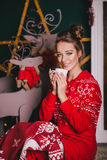 Young beautiful woman in a red warm pajamas with scandinavian ornaments sitting near decorative fireplace and drinking hot tea Stock Photo