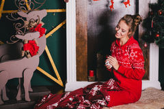 Young beautiful woman in a red warm pajamas with scandinavian ornaments sitting near decorative fireplace and drinking hot tea Royalty Free Stock Images