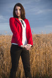 Young beautiful woman in red on a wheat field Stock Photography