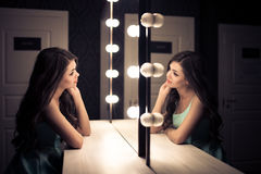 Young beautiful woman and reflection in dressing room Royalty Free Stock Photos