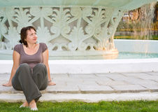 Young beautiful woman relaxes in front of fountain Stock Images