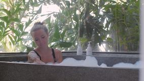 Woman in bath tub. Young, beautiful woman relaxing in the bath with a foam. Pretty girl bathing with pleasure in bathroom with a window and spending time in stock video