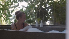 Woman in bath tub. Young, beautiful woman relaxing in the bath with a foam. Pretty girl bathing with pleasure in bathroom with a window and spending time in stock video footage
