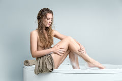 Young beautiful woman relaxing in a bath Royalty Free Stock Images