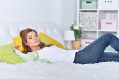 Young beautiful woman relaxing. In bed at home Stock Photos