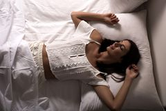 Beautiful woman laying in the bed at night. A young, beautiful woman relaxing in the bed at home at night Stock Photo