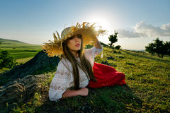 Young beautiful woman relaxing on field in summer Royalty Free Stock Images