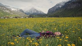 Young beautiful woman is relaxing in flower field against the background of the Swiss Alps. 4k stock video