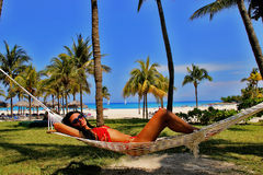 Young beautiful  woman Relaxing In Hammock On The Tropical Beach. And sea background,  Cuba Royalty Free Stock Photos