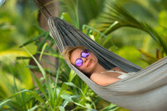 Young beautiful woman relaxing in hammock in a tropical resort. Royalty Free Stock Photo