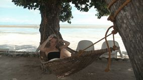 Young beautiful woman relaxing in a hammock. stock video footage